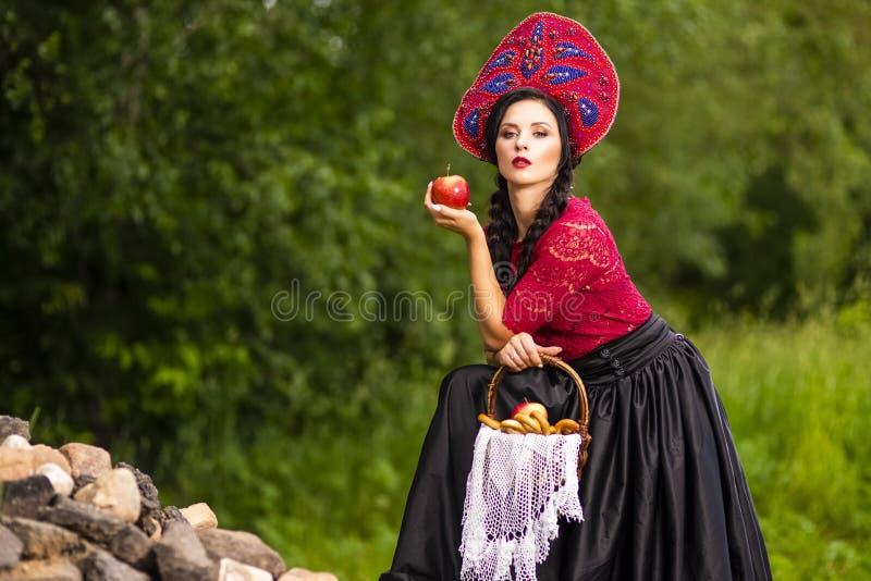 Femme magnifique de Brunete de mode dans l'extérieur russe de Kokoshnik de style Pose avec le panier avec des anneaux de pain sur images libres de droits