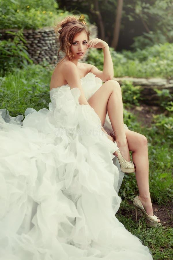 Femme magnifique de jeune mariée avec de longues jambes dans une robe de mariage luxuriante photo libre de droits
