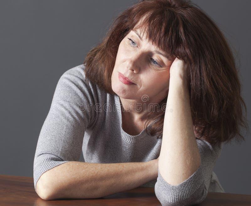 Femme magnifique de pensée des années 50 détendant seule à la maison images stock