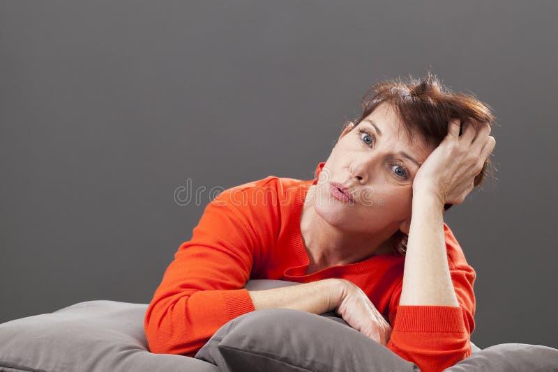 Femme magnifique heureuse des années 50 détendant seule à la maison images stock