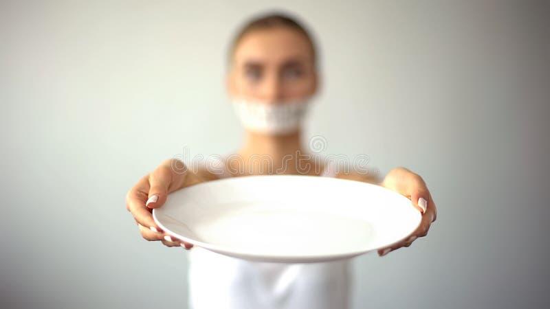 Femme maigre avec la bouche attachée du ruban adhésif montrant le plat vide, concept du jeûne, faim photographie stock