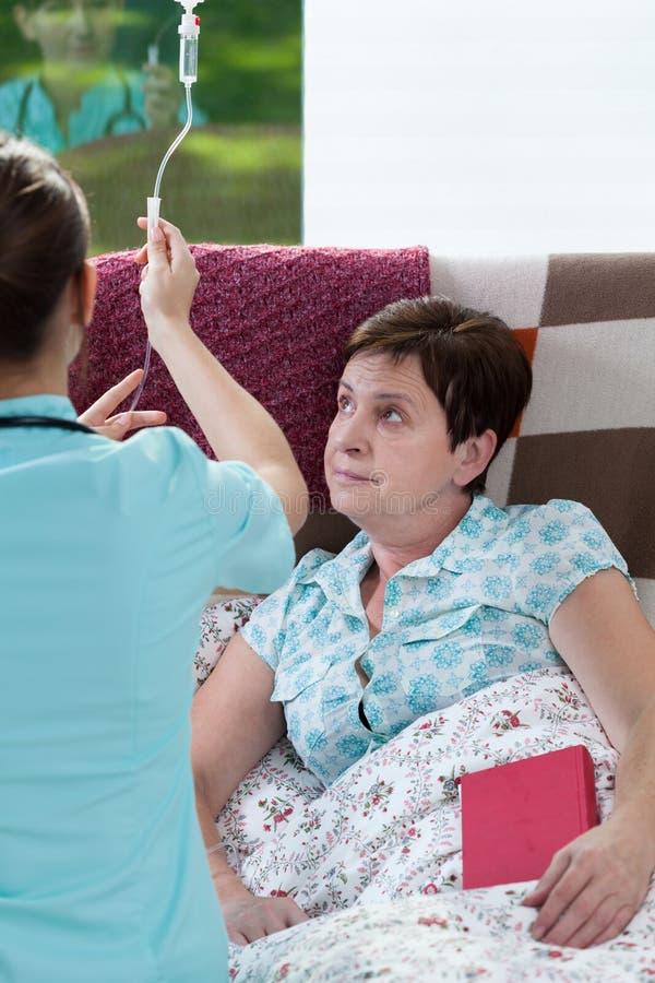 Femme malade étant sur l'égouttement images stock