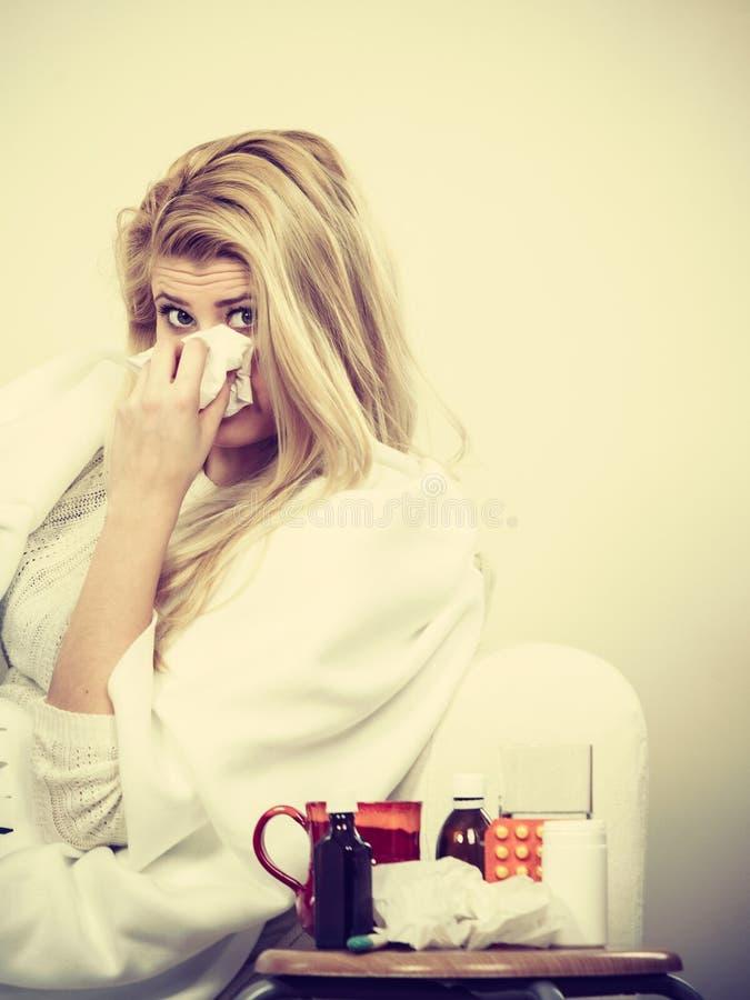 Femme malade éternuant dans le tissu images stock