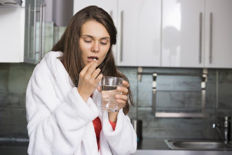 Femme malade prenant la médecine dans la cuisine image libre de droits