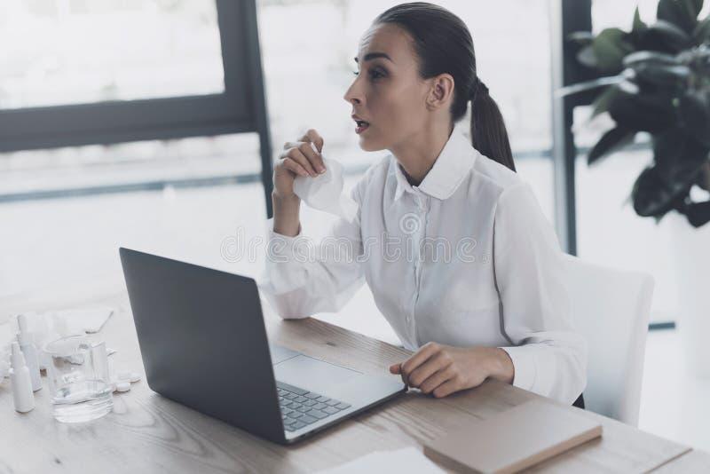 Femme malade s'asseyant sur son lieu de travail dans le bureau Elle tient une serviette dans des ses mains et dispose à éternuer photo stock