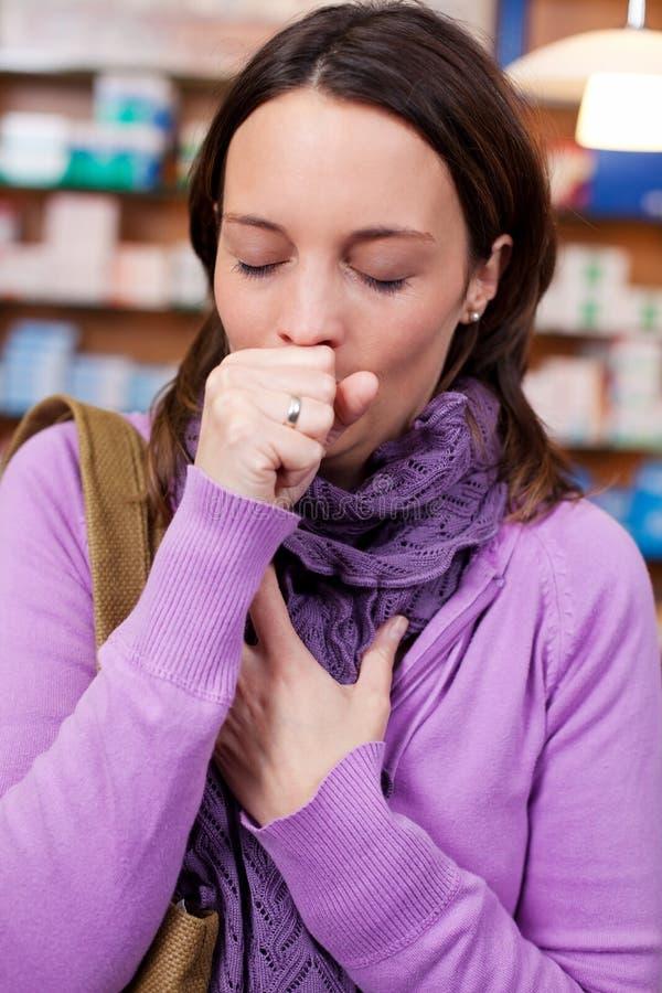 Femme malade toussant dans la pharmacie photographie stock