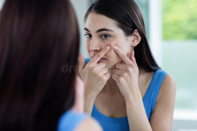 Femme malheureuse avec l'irritation cutanée nettoyant son visage image stock