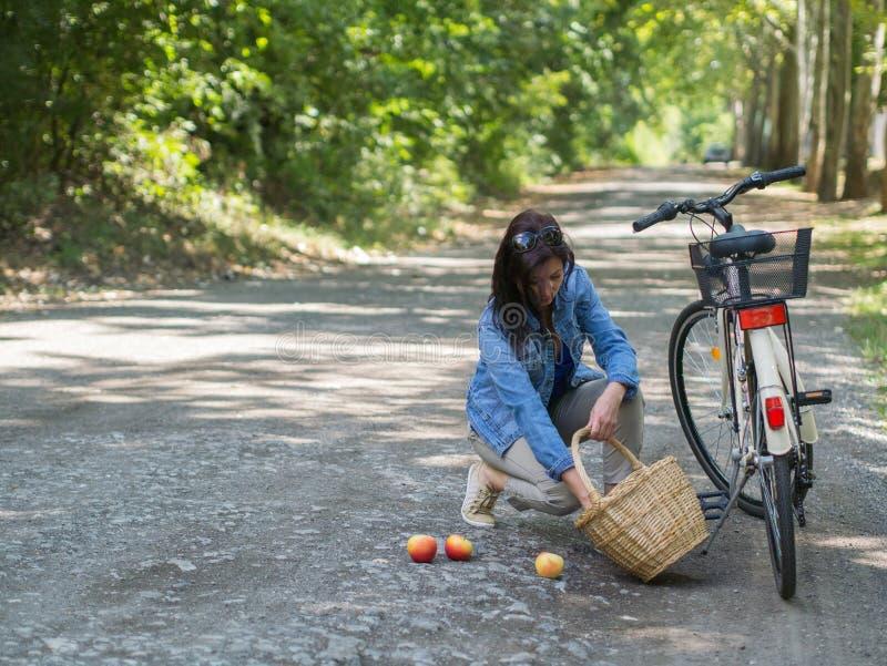 Femme malheureuse avec les pommes renversées photo stock