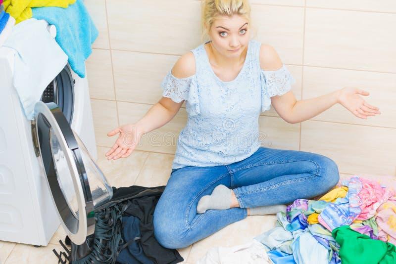 Femme malheureuse ayant beaucoup de blanchisserie photo stock