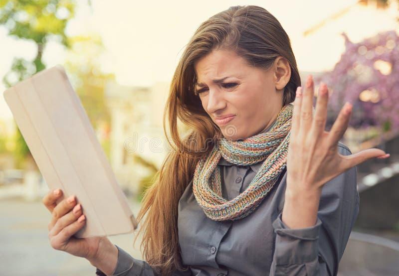 Femme malheureuse confuse avec le comprimé cassé photo stock