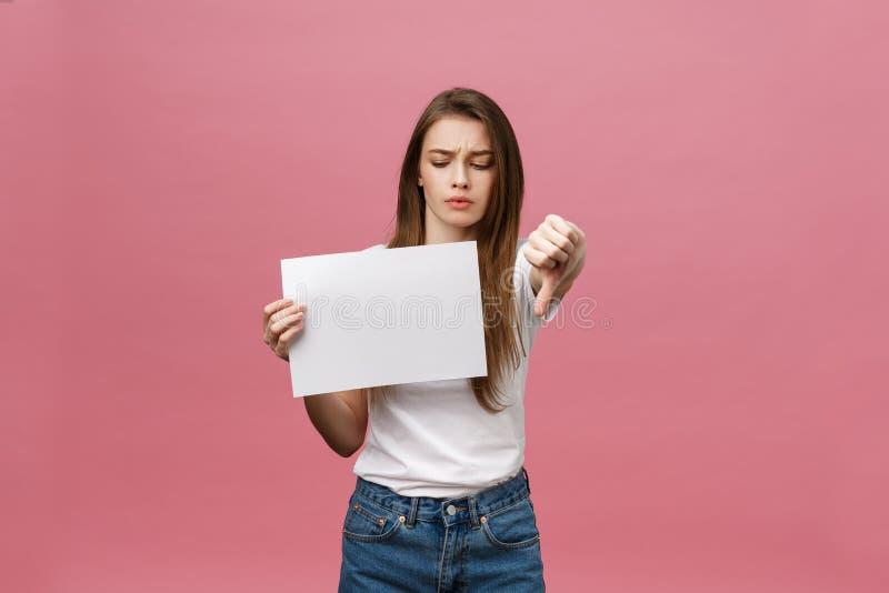 Femme malheureuse donnant des pouces en bas de geste avec le papier blanc et l'expression et la désapprobation négatives photos stock