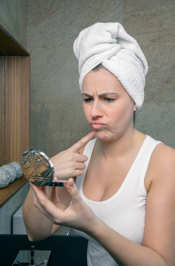 Femme malheureuse regardant un bouton d'acné dans le miroir photos libres de droits