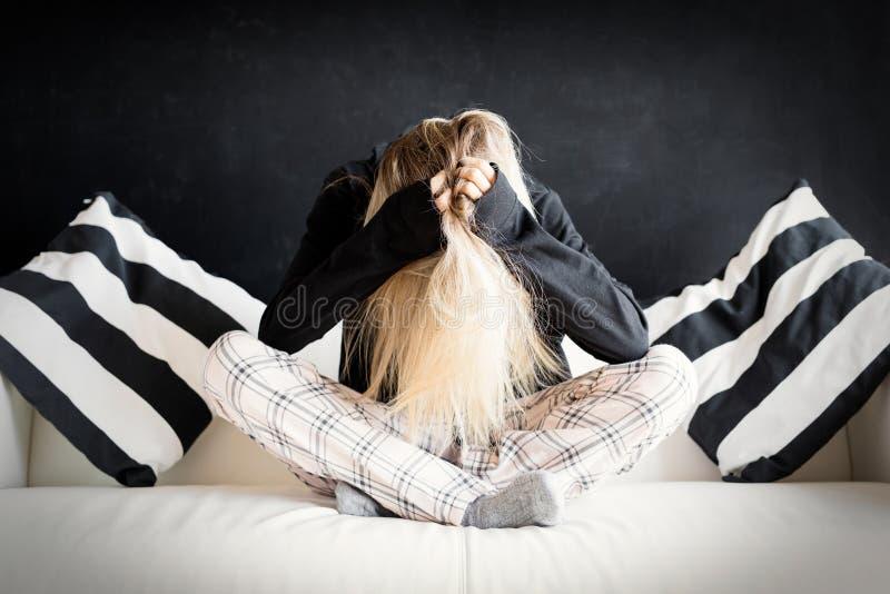 Femme malheureuse s'asseyant dans le divan photographie stock