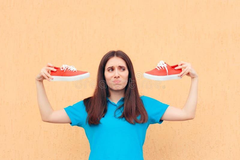 Femme malheureuse tenant une paire de chaussures rouges de sport photos libres de droits