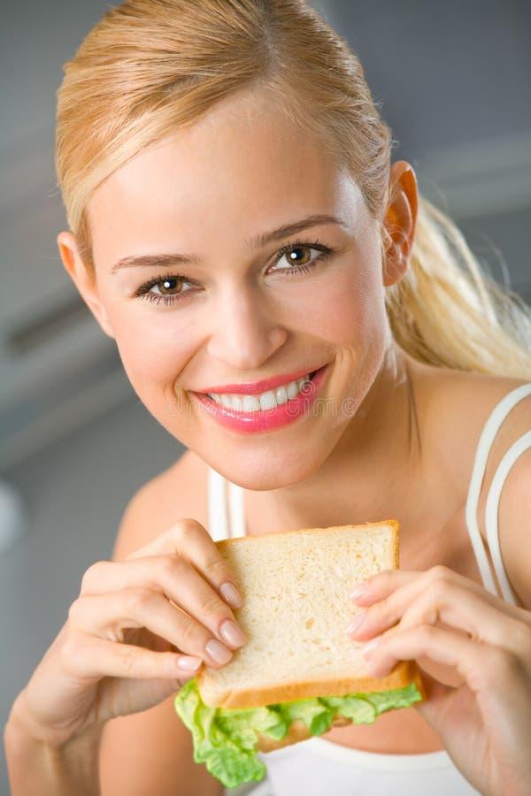 Femme mangeant à la cuisine image stock
