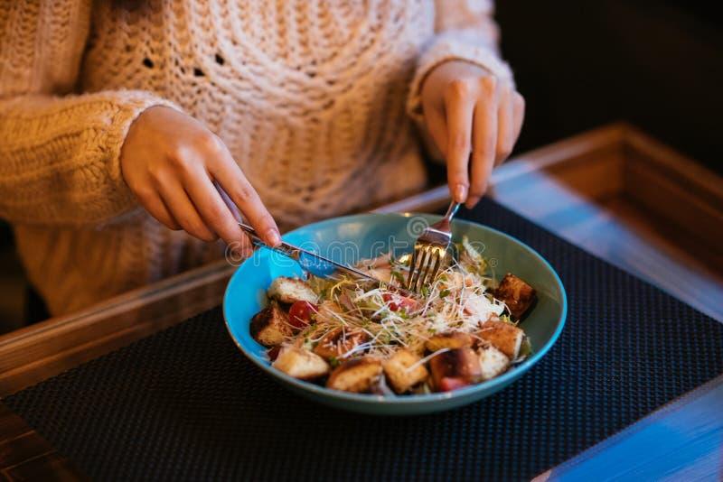 Femme mangeant de la salade de César utilisant des couverts au restaurant photos libres de droits