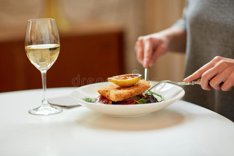Femme mangeant de la salade de poissons au café ou au restaurant photos stock