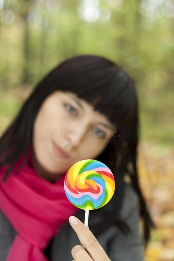 Femme mangeant des lucettes de sucrerie images stock