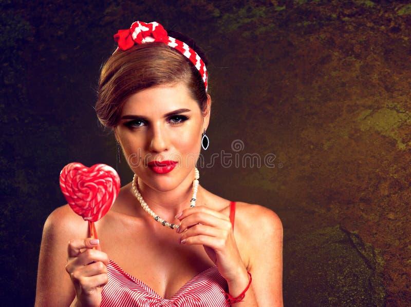 Femme mangeant des lucettes Fille en sucrerie rayée de prise de style de goupille- photographie stock libre de droits