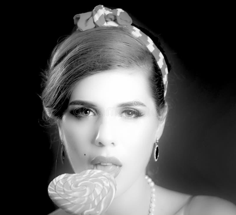 Femme mangeant des lucettes Fille en sucrerie rayée de prise de style de goupille- photographie stock