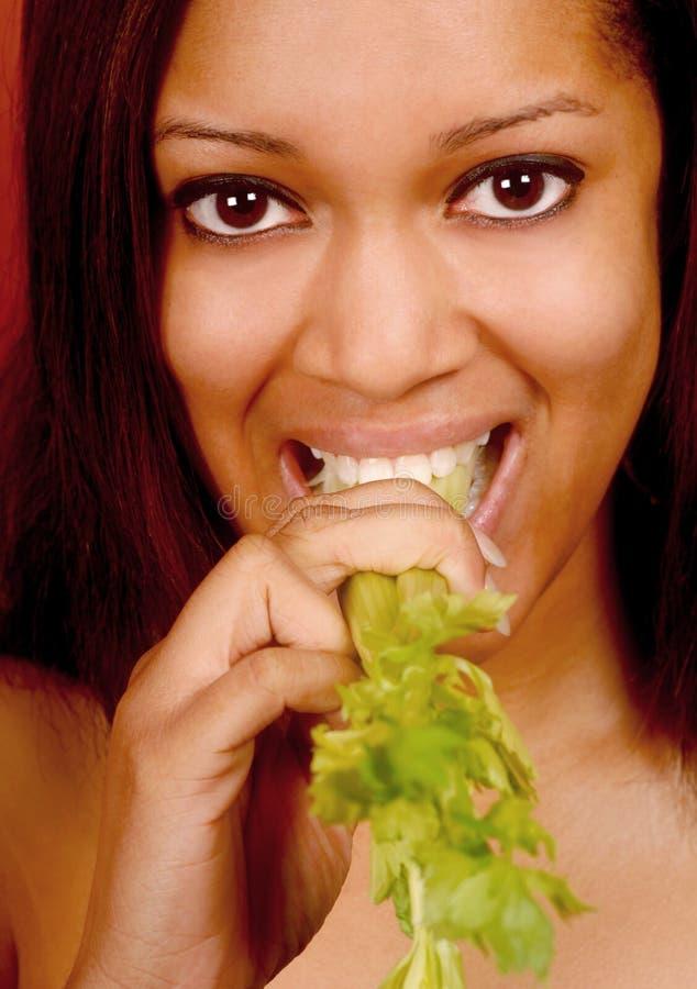 Femme mangeant du céleri images stock