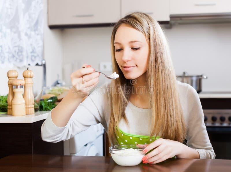 Femme mangeant du formage caillé dans la maison photo stock