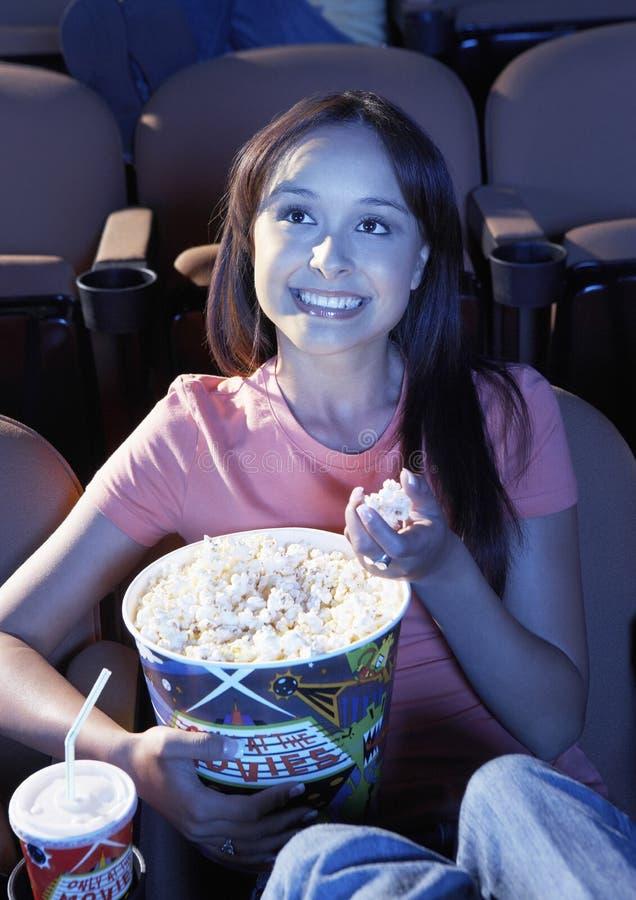Femme mangeant du maïs éclaté tout en observant le film dans le théâtre photographie stock libre de droits