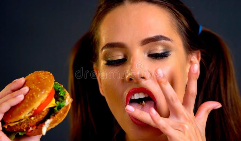 Femme mangeant l'hamburger La fille veut manger des aliments de préparation rapide images stock