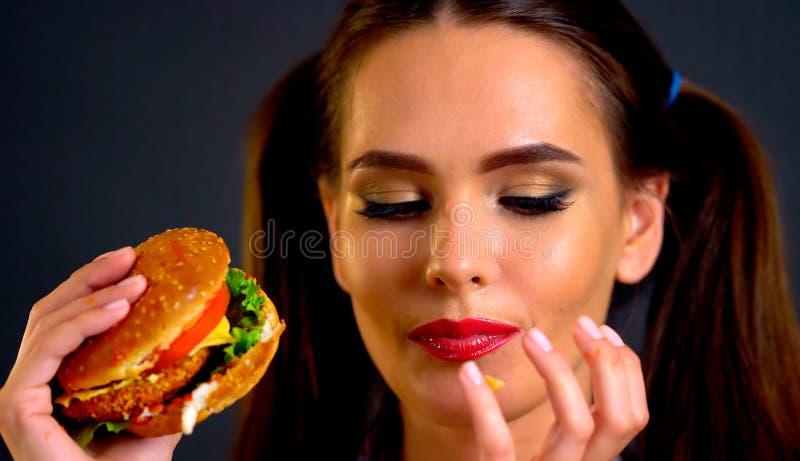 Femme mangeant l'hamburger La fille veut manger des aliments de préparation rapide image stock