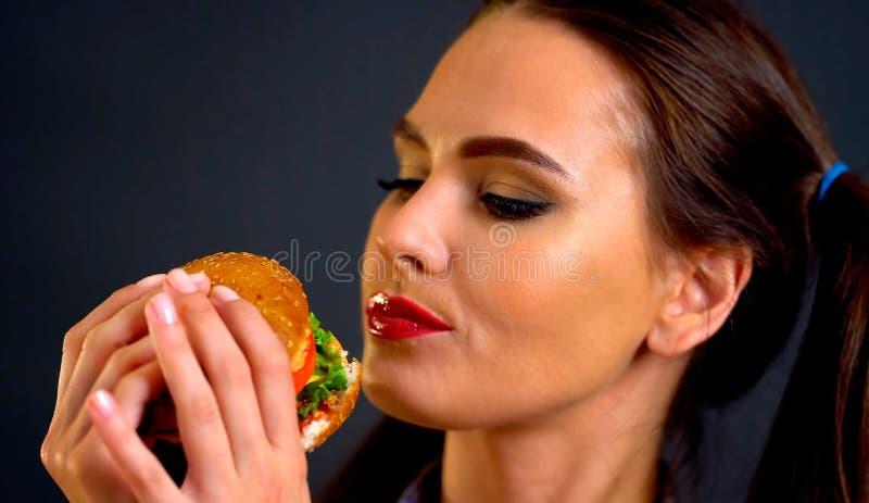 Femme mangeant l'hamburger La fille veut manger des aliments de préparation rapide images libres de droits
