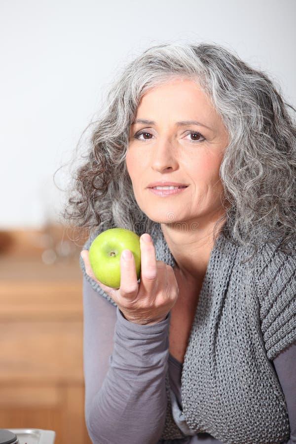 Femme mangeant la pomme verte images libres de droits