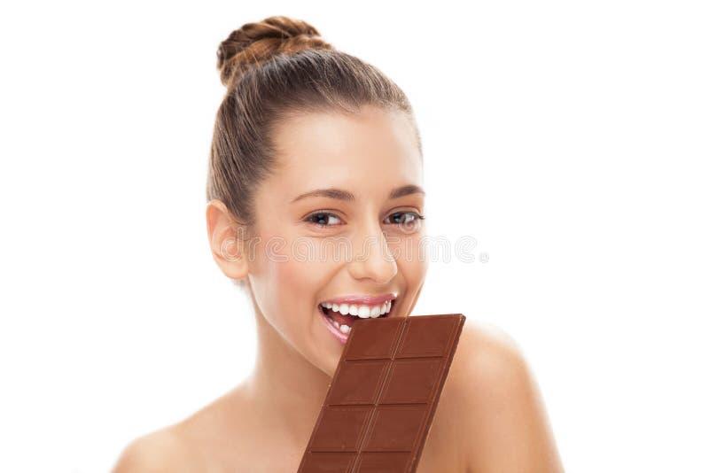 Femme mangeant le bar de chocolat photographie stock