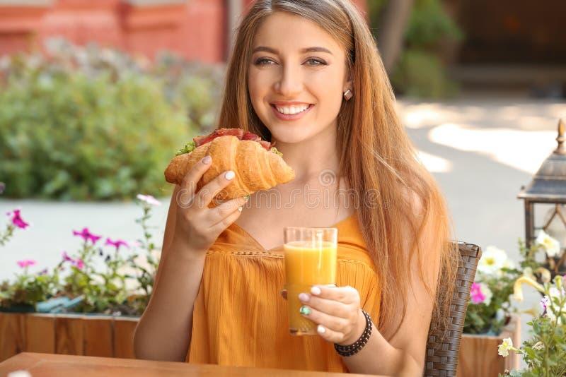 Femme mangeant le croissant savoureux et buvant du jus en café dehors photos libres de droits