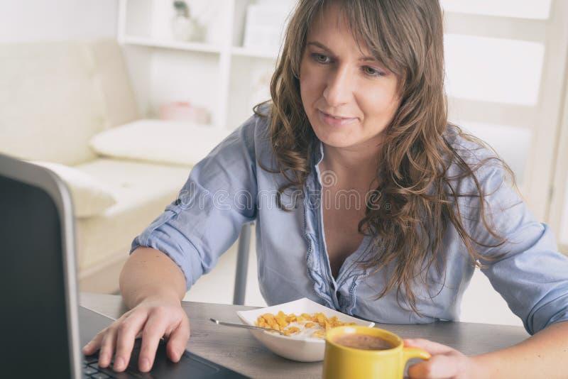 Femme mangeant le déjeuner à la maison images libres de droits