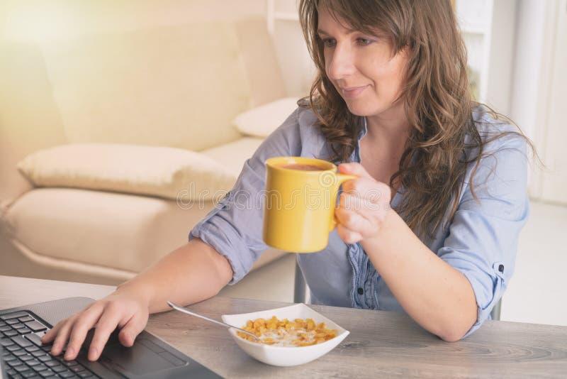 Femme mangeant le déjeuner à la maison images stock