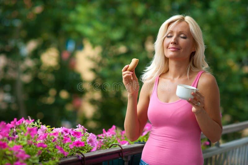 Femme mangeant le déjeuner sur le balcon images stock