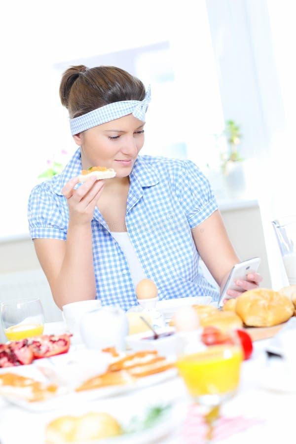 Femme mangeant le petit déjeuner et textoter image stock