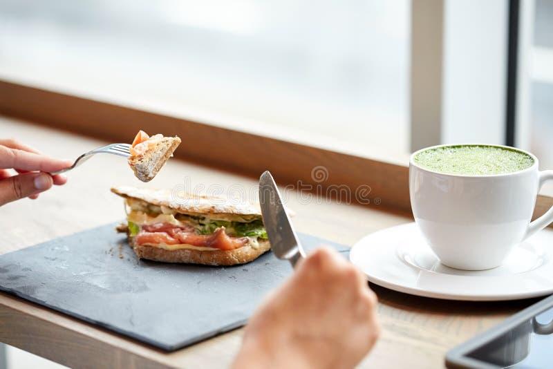 Femme mangeant le sandwich saumoné à panini au restaurant images stock