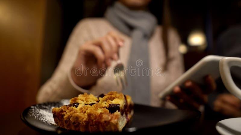 Femme mangeant le tarte d?licieux et ? l'aide du t?l?phone, appr?ciant seul le temps libre, fin  photos stock