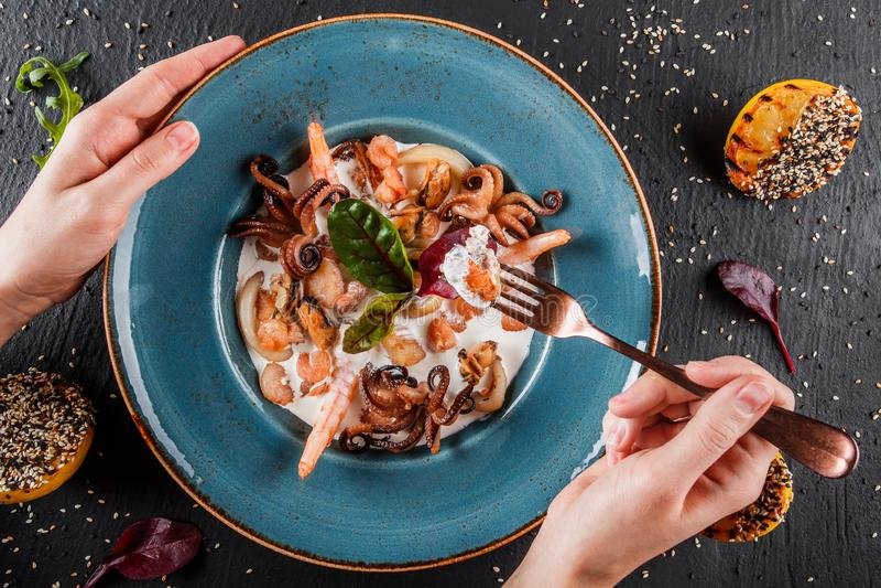 Femme mangeant les crevettes roses frites, moules, calamari, seiche, poulpe avec de la sauce cr?me dans le plat sur le fond en pi photographie stock