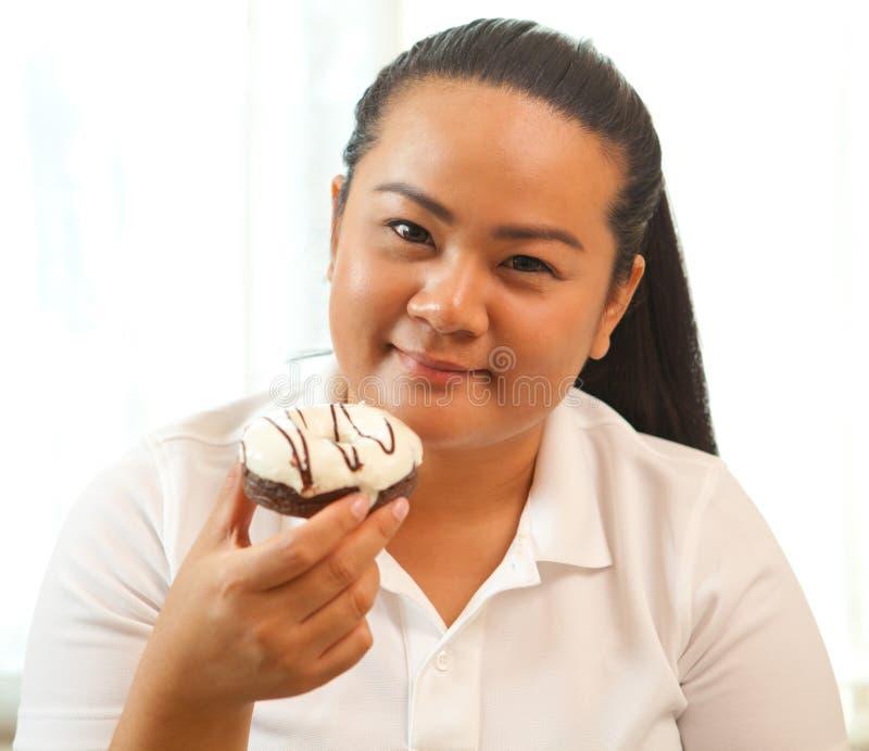 Femme mangeant un beignet photo libre de droits