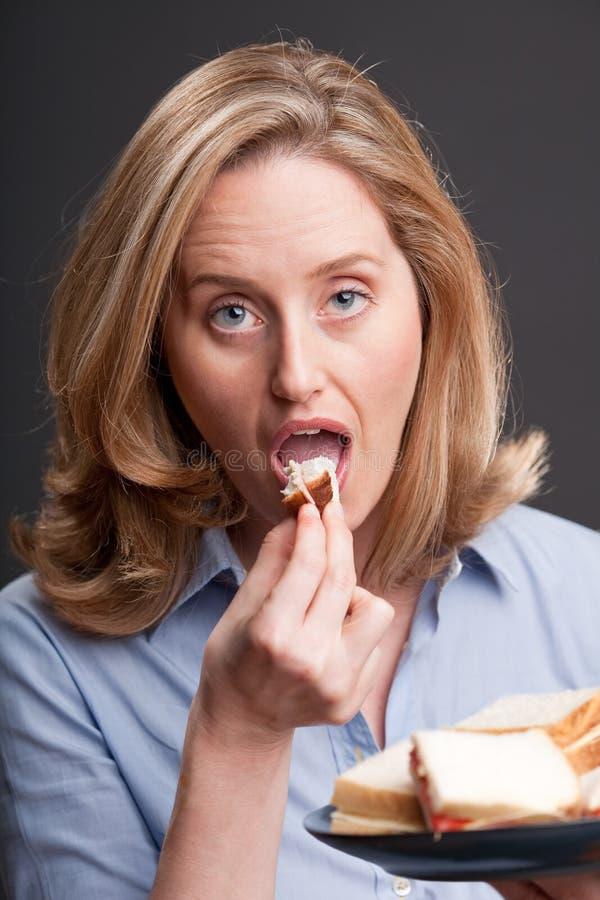 Femme mangeant un sandwich photo stock