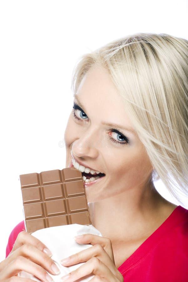 Femme mangeant une barre de tentation de chocolat images libres de droits