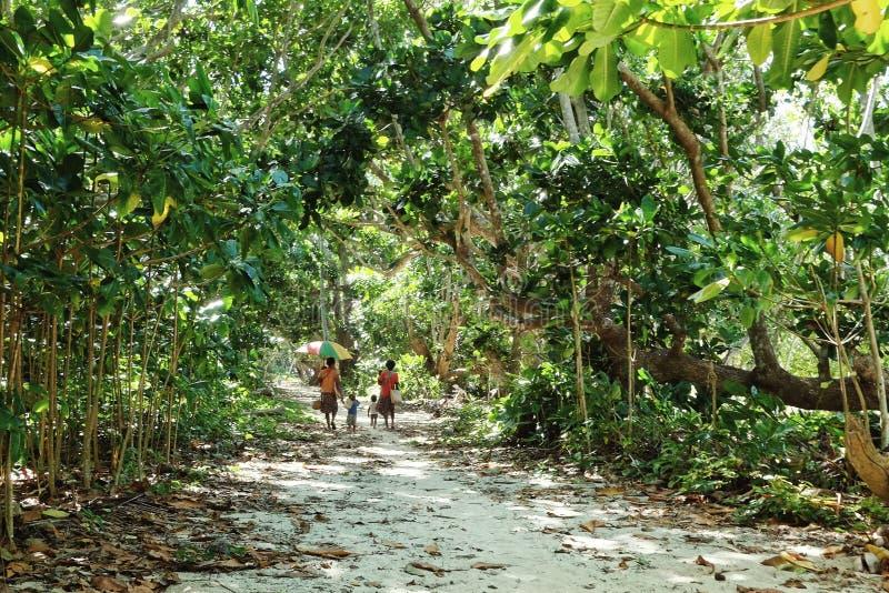 Femme marchant à la maison avec des enfants sur le chemin de bord de mer à côté de leur village photo stock