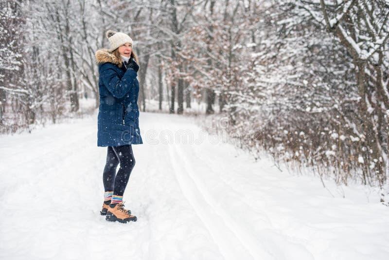 Femme marchant au pays des merveilles de forêt d'hiver le jour neigeux photo stock