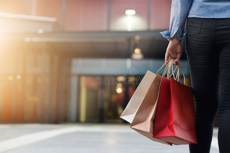 Femme marchant avec des paniers sur le fond de centre commercial images stock