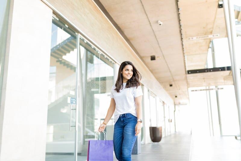 Femme marchant avec des sacs en papier dans le centre commercial photographie stock libre de droits
