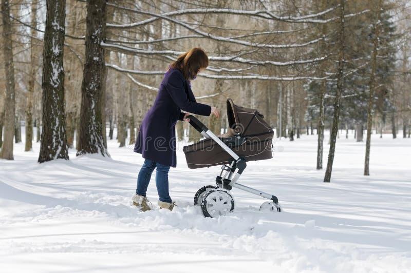 Femme marchant avec la voiture d'enfant images libres de droits