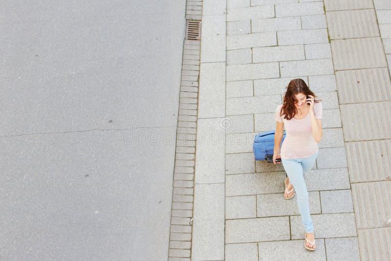Femme marchant avec le sac et parlant au téléphone portable image libre de droits