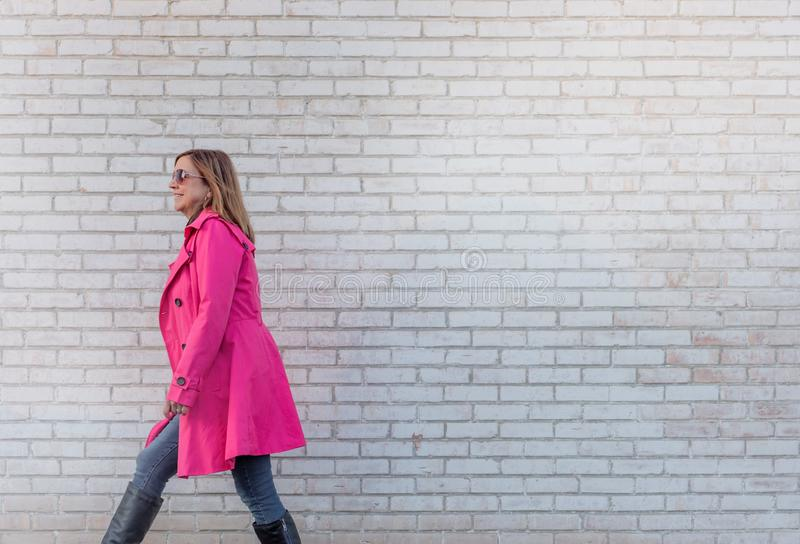 Femme marchant contre le mur de briques - surexposé pour l'effet image libre de droits